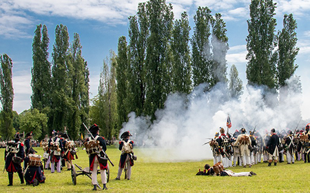 reanactment of a battle with people dressed in the time's dress.